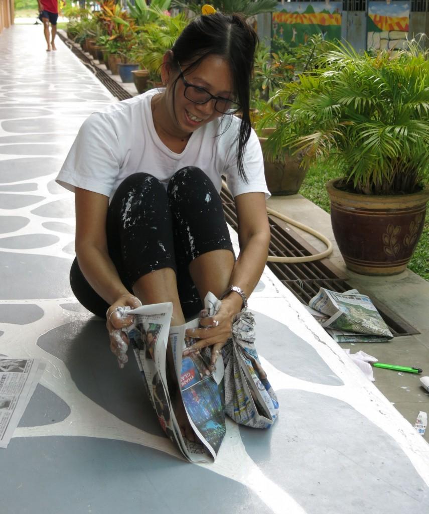 戴舒娟在油漆地面之前,先作好准备用报纸包住双脚,以免弄脏脚板。
